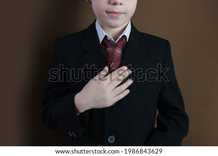 close-up of the lower part of the head of a child 8-10 years old, kid in a black business suit, tie smiling, formal uniform, concept of a young businessman, performance Royalty-Free Stock Photo #1986843629