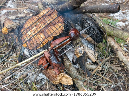 picture with snowy background and picnic accessories, campfire and iron skewers with sausages and pancakes for baking on the campfire in winter, tourist lunch by the nature in winter