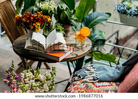Reading books in summer at a beautiful terrace or cozy balcony full of green plants. Royalty-Free Stock Photo #1986877016