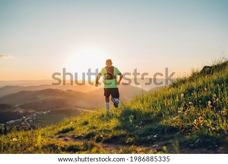 Active mountain trail runner dressed bright t-shirt with backpack running endurance marathon race by picturesque hills at sunset time back view photo. Sporty active people backlight concept image.