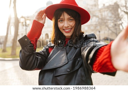Close up of a smiling young stylish brunette white woman wearing hat and leather jacket with short hair standing on a street taking selfie