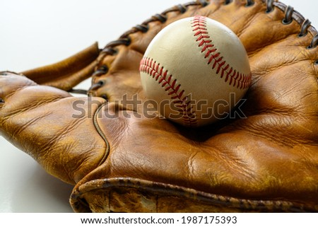 A white leather baseball in a brown vintage, antique glove Royalty-Free Stock Photo #1987175393