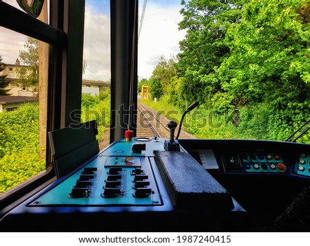 Tram cabin, streetcar cabin or trolley cabin with a view through the window to the outside of the tracks and the outside view Royalty-Free Stock Photo #1987240415