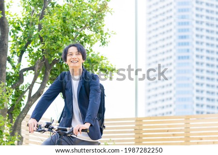 Young asian man riding a bicycle. Royalty-Free Stock Photo #1987282250