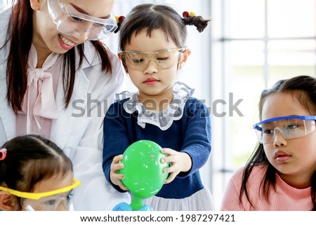 Portrait closeup shot of Asian little curious elementary girl with bunches pigtail hairstyle wears safety goggles looking at water bottle blowing green rubber balloon experiment teach by teacher. Royalty-Free Stock Photo #1987297421