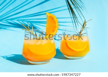 Close-up lemonade, orange cocktail, refreshing summer drink with ice in a glass with a sprig of rosemary on a blue background under a palm leaf on a bright sunny day. Royalty-Free Stock Photo #1987347227