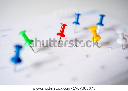 Push pins on calendar, mark the Event day with a red pin. Close-up of red pins. Royalty-Free Stock Photo #1987383875