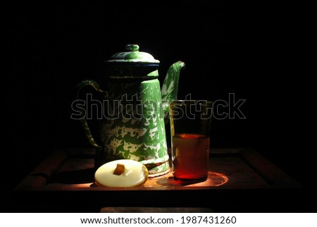 picture of indonesia vintage traditional enamel tea pot with similar green camouflage pattern on a wooden tray.