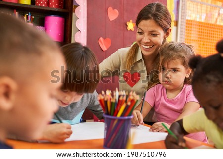 Kindergarten teacher taking care of children while painting pictures in the painting course