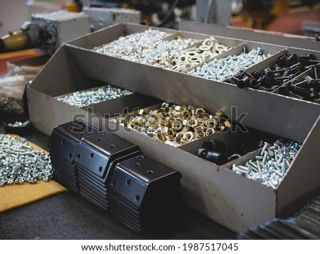 Different types of fasteners on the worker's table. Work place at the assembling shop. Bolts and nuts Royalty-Free Stock Photo #1987517045