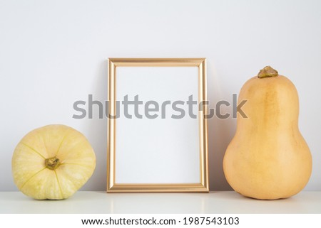 Autumn frame, background. Thanksgiving mockup with golden vertical frame and yellow pumpkins. Halloween, fall minimal composition.