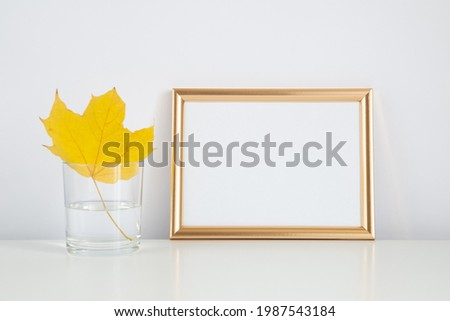Autumn frame, background. Thanksgiving mockup with golden frame and yellow leaf. Halloween, fall minimal composition.