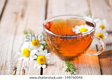 cup of tea with chamomile flowers on rustic wooden background #198760046