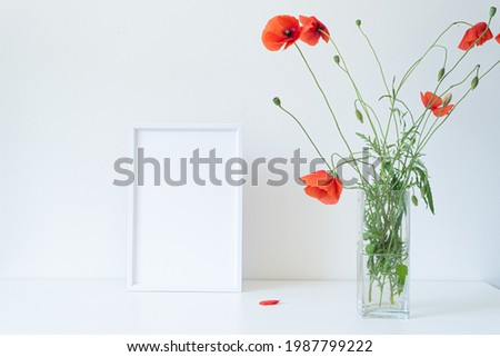 Empty white picture frame mockup. Glass vase with beautiful wild poppy flowers on white table. Lively and cheerful summer still life scene. Happy day concept