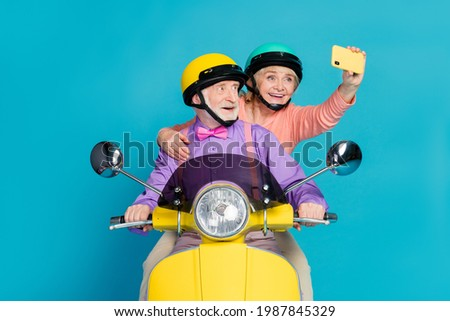 Photo of grey haired retired pensioner husband wife couple people wear helmet rider make selfie isolated on blue color background Royalty-Free Stock Photo #1987845329