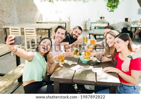 Selfie to remember this moment. Excited college friends taking a picture with a smartphone while hanging out and drinking beers at a bar