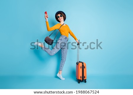 Full length body size photo girl keeping cellphone in airport terminal ready to travel with baggage isolated vivid blue color background