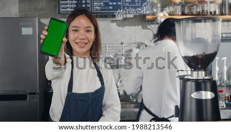 Asian happy beautiful young woman standing behind the bar counter in cafe smiling showing smartphone blank green screen looking camera, small business owner coffee shop