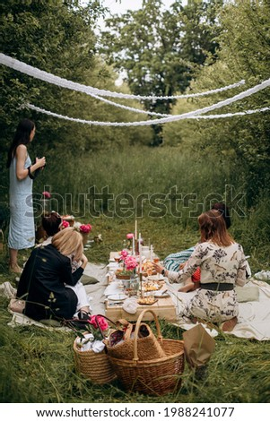 female summer outdoor picnic in the garden. picnic pallet table with drinks and snacks. picnic party in a decorated place in the garden with girlfriends