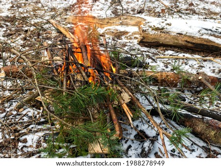 picture with snowy ground background and picnic accessories, small campfire and iron grill for cooking on the campfire tourist lunch in nature in winter