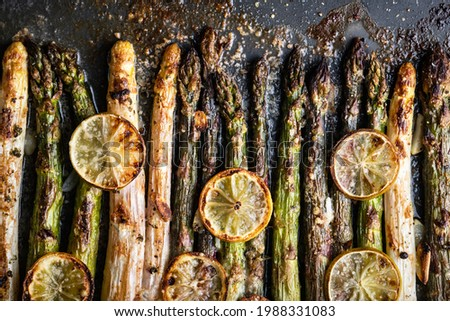 Baked white, purple and green asparagus sprouts vegetables with lemon, garlic and cheese on a dark background. Food photography