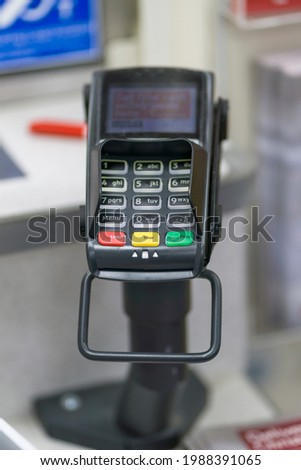 A Photograph of a Credit Card Machine in a Shop or Store when a  Customer is Purchasing From The Store at The Checkout