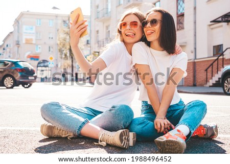 Two young beautiful smiling hipster female in trendy summer white t-shirt clothes and jeans.Sexy carefree women posing on the street background.Positive models show tongue, hugging.Taking photo selfie
