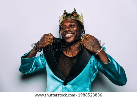 portrait of an hip hop music musician. Cinematic image of a man wearing party clothes and jewels