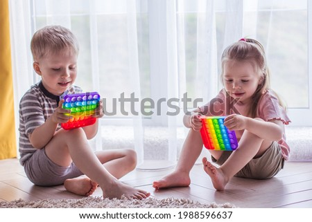 Blonde boy and girl Kids play with pop it sensory toy. Trendy silicon fidgeting game for stressed children and adults. Squishy soft bubble toys. Kid playing with rainbow color pop-it Royalty-Free Stock Photo #1988596637