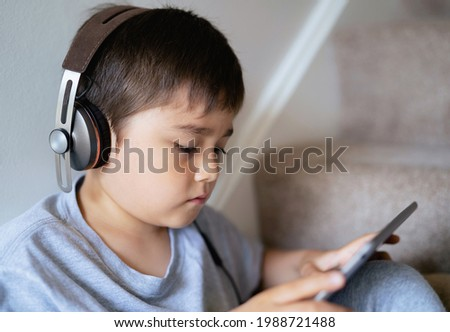 Closeup face of young boy wearing headphone listening to music, Child sitting on staircase carpet playing game on digital pad.Cute kid relaxing at home watching cartoon on tablet.