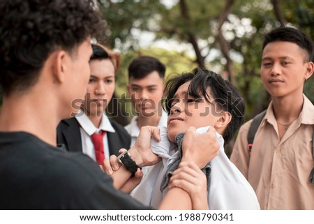 A bunch of high school delinquents bully a smaller boy. One bully grabs him by the collar. Emotional and physical abuse issues in teenagers. Royalty-Free Stock Photo #1988790341