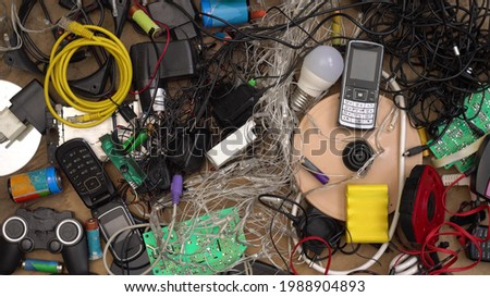 E-waste and Hazardous waste sorting and disposal. Old broken phones, battery, computers and electronics. Heavy metal pollution. Used electrical devices and obsolete electronic equipment Royalty-Free Stock Photo #1988904893