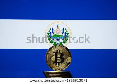 Bitcoin representation coin placed in front of blurred Salvador's national flag. El Salvador is the first country to adopt bitcoin as legal tender. Concept. Royalty-Free Stock Photo #1988913071