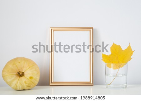 Autumn frame, background. Thanksgiving mockup with golden frame and yellow leaf and pumpkin. Halloween, fall minimal composition.