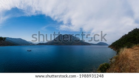 Calm sea with boats and big mountain. Adrasan, Antalya, Turkey. May 2021. Panoramic picture