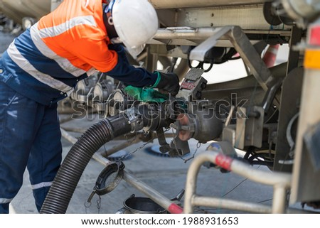 A tanker truck driver delivers gasoline to a gas station Royalty-Free Stock Photo #1988931653