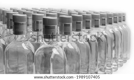 Bottles of pure alcohol not labeled. Multitude Bottles of Home Alcoholic Beverages Isolated On White. Small liquor production based on distillation. Bottles empty full  placed in a row.   Royalty-Free Stock Photo #1989107405