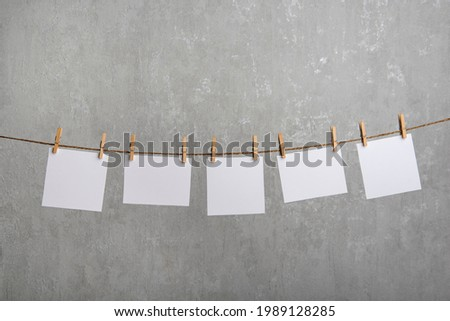 Blank paper notes hang with clothespins on rope. Grey background. Copy space. Royalty-Free Stock Photo #1989128285
