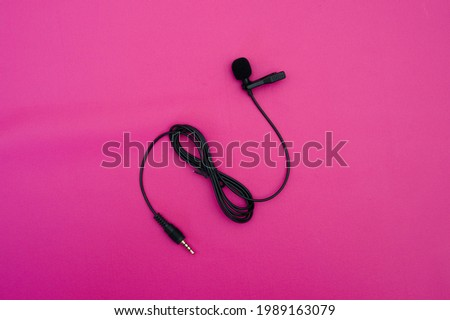 clip on mic on pink background. clip on microphone with wire captured on pink. minimal object shot. Royalty-Free Stock Photo #1989163079