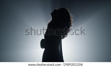 Silhouette of beautiful girl standing in spotlight background. Side view of young woman looking up in dark space. Attractive female person moving hands in air indoors.  Royalty-Free Stock Photo #1989201206