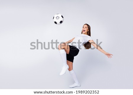Full body photo of excited lady player soccer team kick leg control ball showing freestyle tricks wear football uniform t-shirt shorts boots knee socks isolated white color background