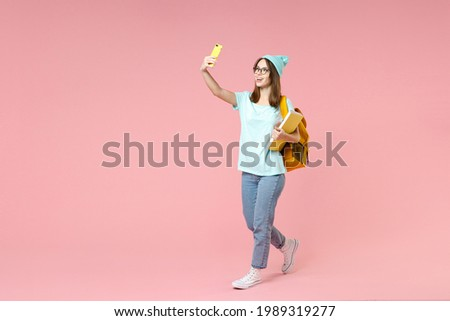 Full length side view of funny woman student in t-shirt hat glasses backpack hold notebooks doing selfie shot on mobile phone isolated on pink background. Education in high school university concept