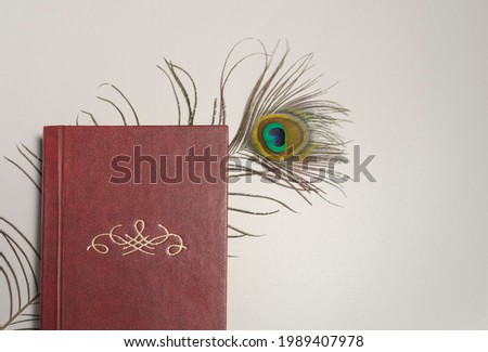 Old brown book in composition with peacock feather on white background
