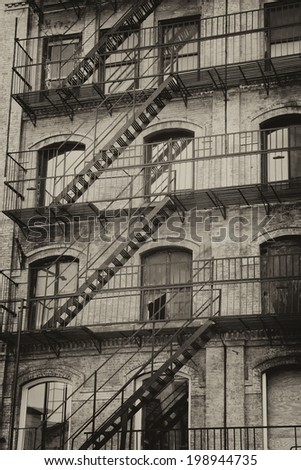 Vintage photo of old building with outdoor staircase (New York City, USA).Vertically. Processed as a vintage photo.