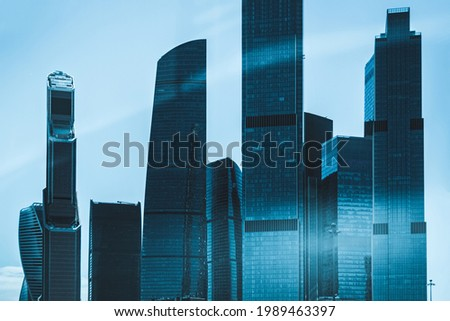 Silhouettes of business skyscrapers and modern office buildings against the blue sky with sunlight. Business and economy concept. Copy space for your design.