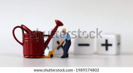 A miniature man carrying a red watering can with a handcart and a white cube with arithmetic symbols. Miniature people and business concept. Royalty-Free Stock Photo #1989574802