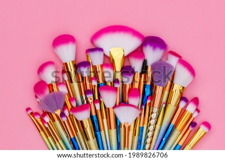 Professional Make up colorful Brushes on pink  background, close up. Cosmetic Makeup Brush Set.