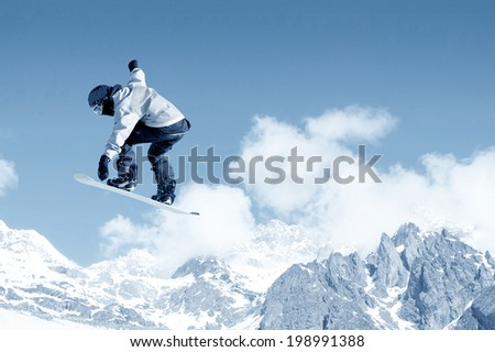 Snowboarder making jump high in clear sky #198991388