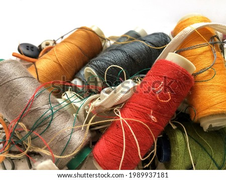 Piles of colorful threads mixed with sewing equipment, looks messy Royalty-Free Stock Photo #1989937181