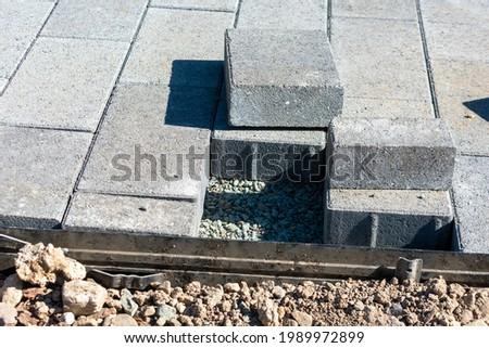 Gray stone pavers installation in progress. Cut paving stones, edge restraints, gravel base Royalty-Free Stock Photo #1989972899